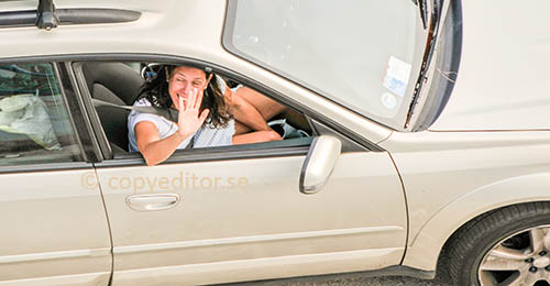 A woman in a car is waving goodbye through the side window