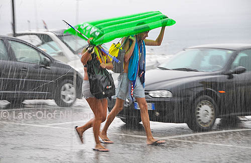 A couple is walking through heavy rain trying to protect themselves with an inflatable air mattress