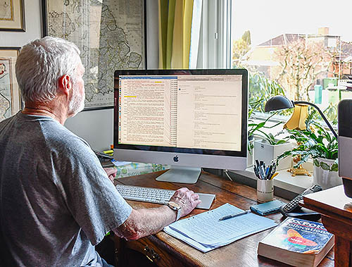 Man writing on a desktop computer. Is he a copy editor, a copy-editor or a copyeditor?