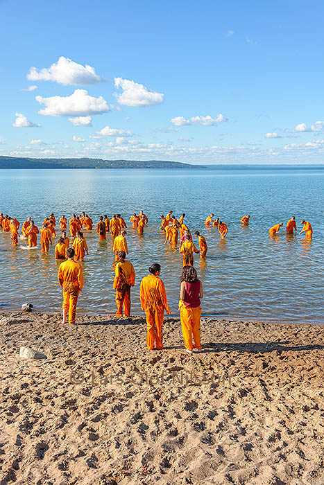 A number of people dressed in orange are wading out into a lake