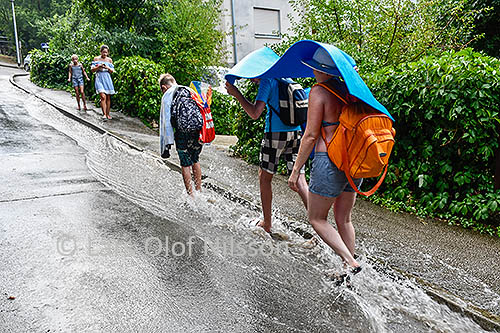 A family is walking in a gutter covering themselves against a heavy rain