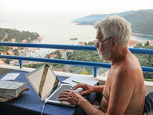 A man on a balcony overlooking the sea is writing on his laptop
