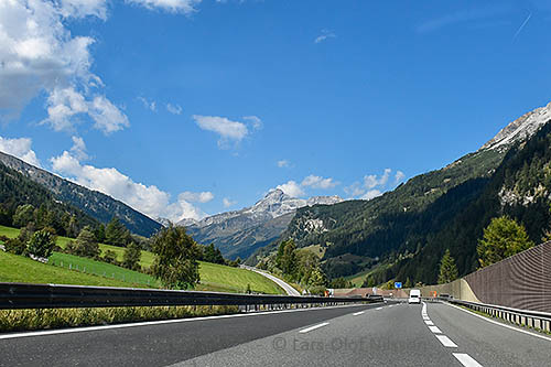 A landscape with a motorway in the foreground and mountains in the background against a blue sky
