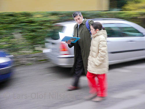 While walking to school a father is checking his daughter's knowledge to see if she has done her homework