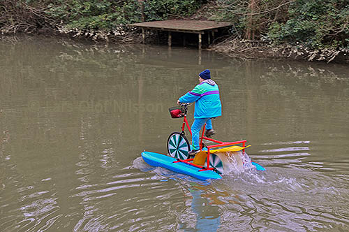 A man is cycling on a river wearing sensible weatherproof clothing