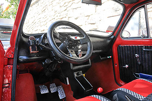 Interior of a red Fiat 500 with steering wheel,  dashboard and pedals visible
