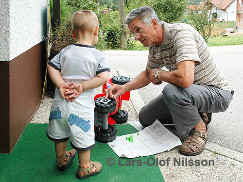 A grandfather is helping his grandson with a toy car