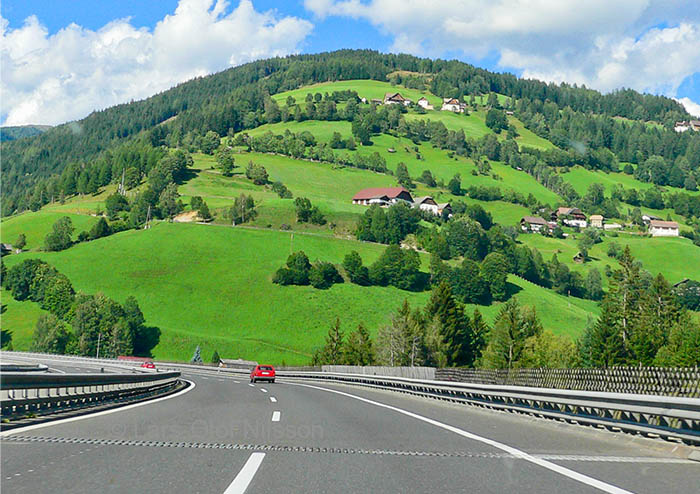 Just a couple of cars on the Autobahn in Austria with some farm buildings on a hill in the background