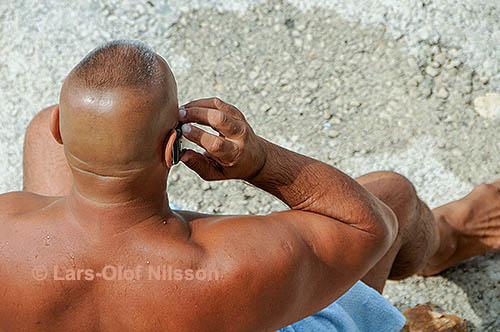 Burly man on a beach speaking on a cellphone. He is enquiring about renting a sunshade.