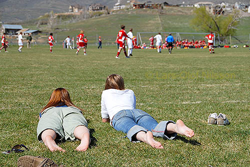 Two girls lying on the grass watching a soccer game.
